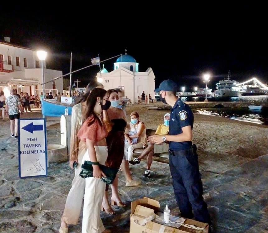 Aστυνομικοί μοιράζουν μάσκες στους επισκέπτες της Μυκόνου